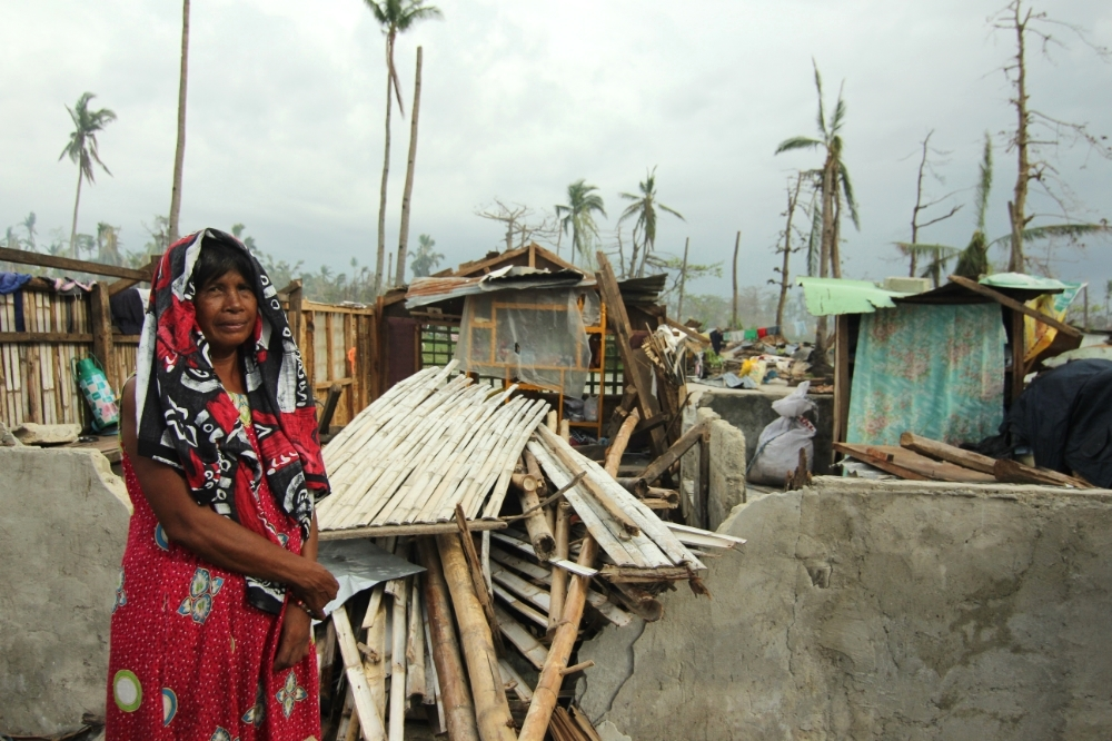 A woman in front of her home after typhoon Haiyan during missions trip to the Philippines