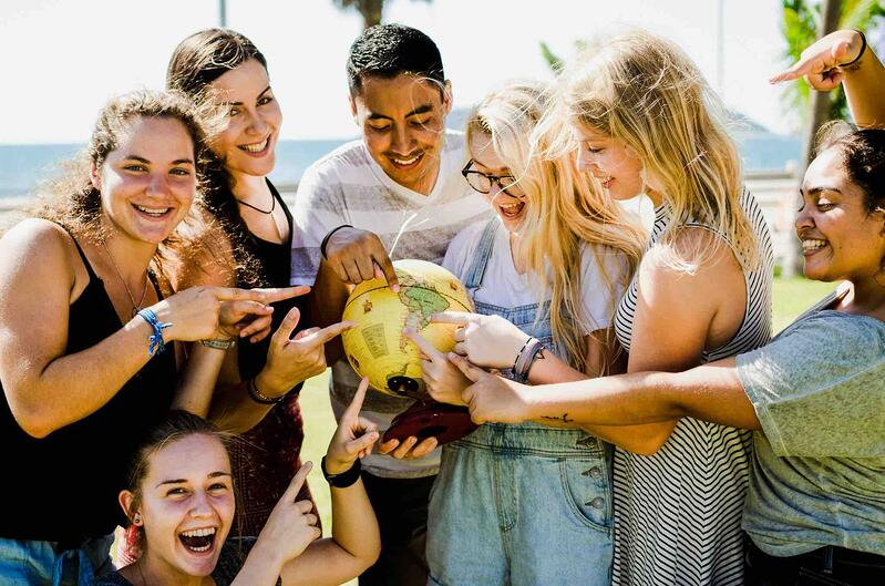 YWAM missionary team surrounding and pointing at a globe of the world