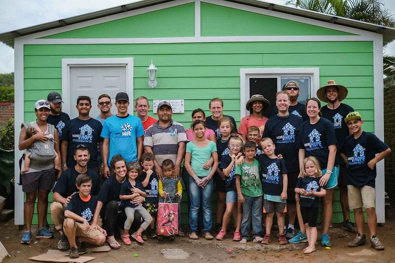 A Homes of Hope team and the recipient family standing in front of the finished home they just built for a family in Mazatlan