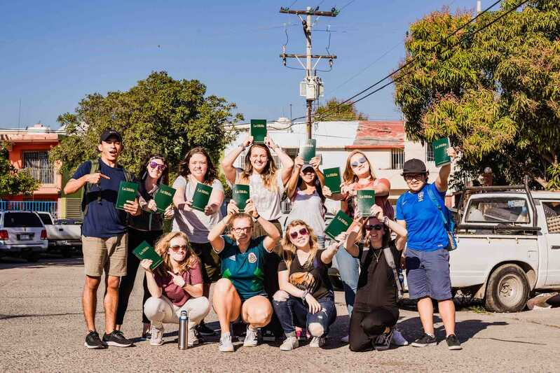 Smiling group of YWAM Mazatlan missionaries holding up Bibles as they head out to do Bible distribution in Mazatlan, Mexico
