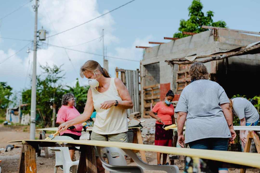 YWAM Homes of Hope volunteer woman paints siding on a build site