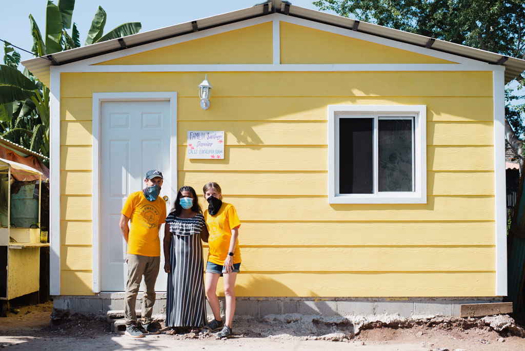 YWAM Homes of Hope volunteers standing in front of newly built home with recipient woman in Mazatlan