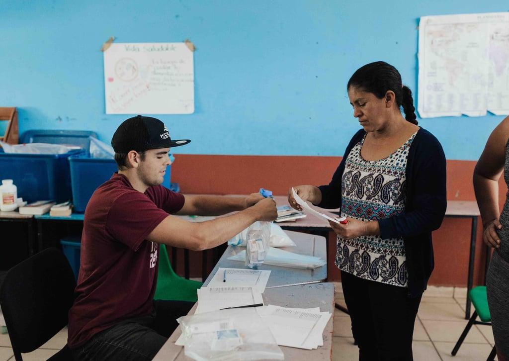 Young volunteer missionary filling a prescription for Mexican woman at a YWAM Mazatlan medical bridage
