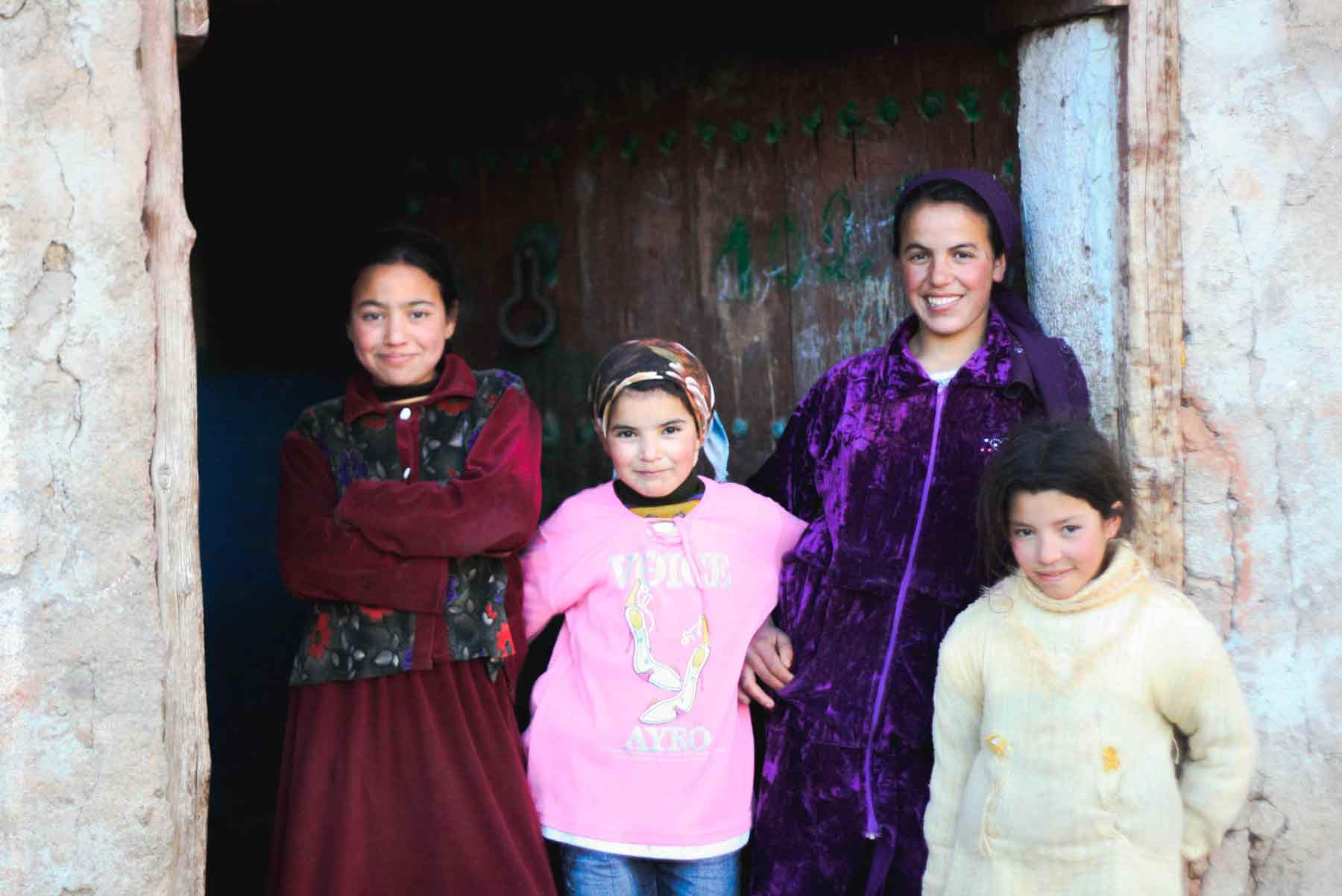 Middle Eastern women standing outside their home and smiling